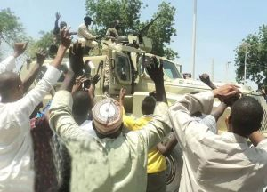 Residents rejoice with Nigerian Soldiers returning from a successful routing of Boko Haram militants in Konduga near Maiduguri.